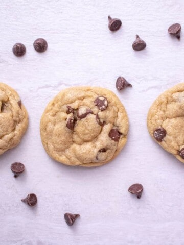 3 chocolate chip cookies in a row with chocolate chips sprinkled around on a light gray background, overhead shot.