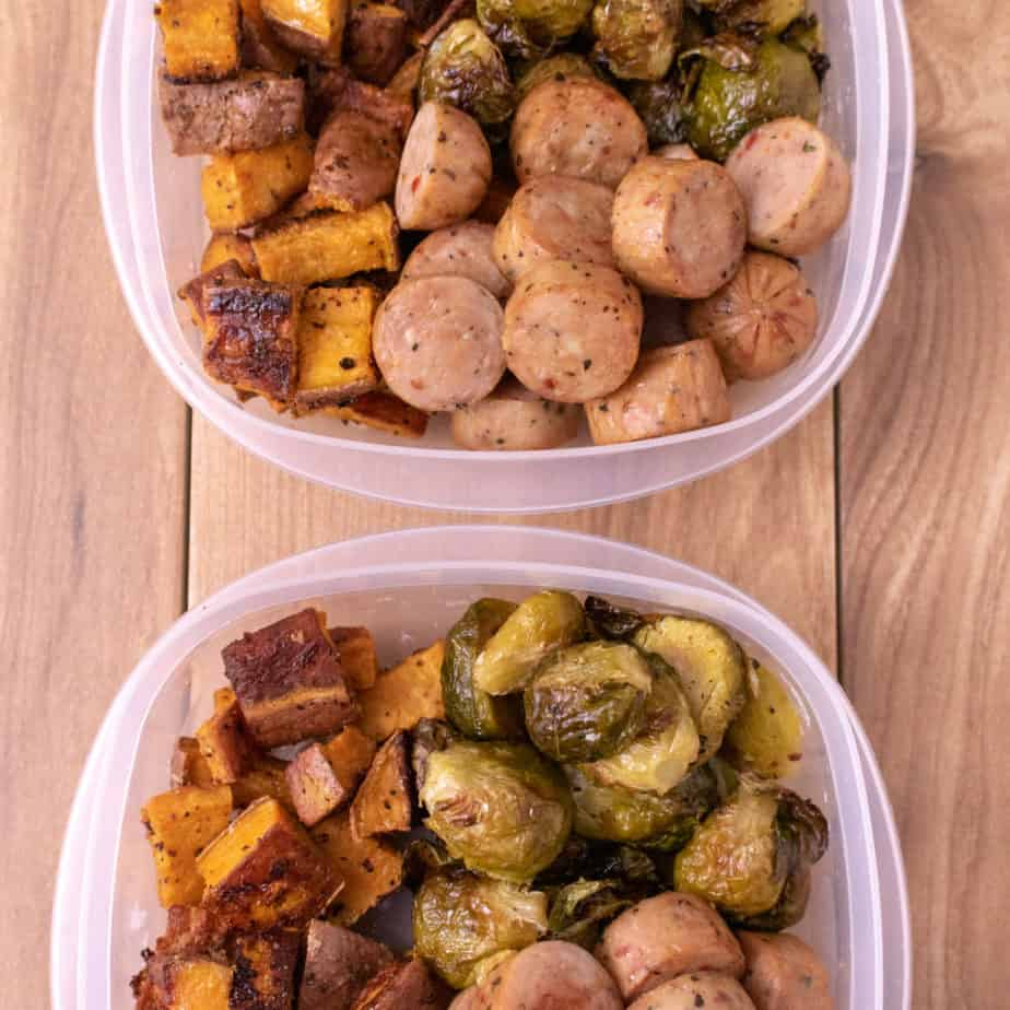 Overhead shot of 2 containers of chicken sausage cut into coins, roasted brussel sprouts and roasted sweet potatoes in a clear plastic container. On a wood back ground