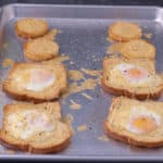 4 Pieces of toast with eggs in the middle on a sheet tray.