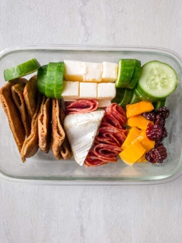 On a light gray background, a glass container holds pita chips, cut up cucumbers, cubed pieces of cheddar, a slice of brie, some folded salami, dried craisins and dried mango.