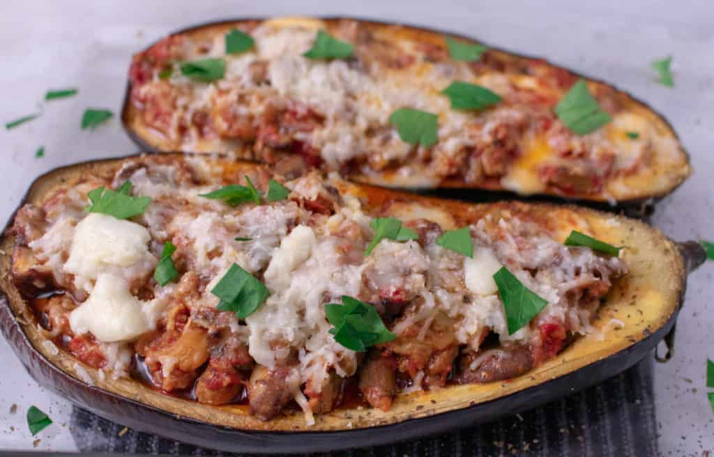 2 halves of eggplant, roasted and stuffed with sausage, pastas sauce and cheese. Topped with parsley in a glass pyrex container. Overhead shot.
