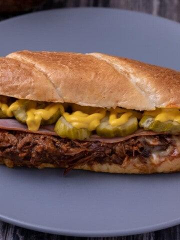 BBQ pulled pork cuban sandwich on a blue plate.