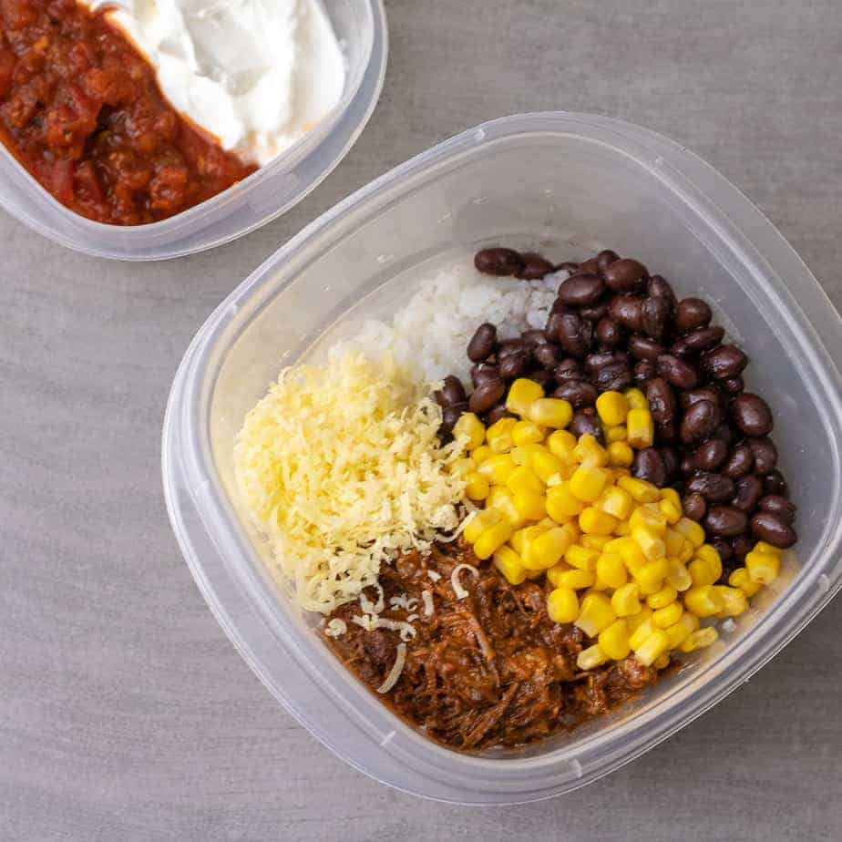 White rice, black beans, corn and pulled pork in on plastic storage container. Sour cream and salsa in the background in a separate container.