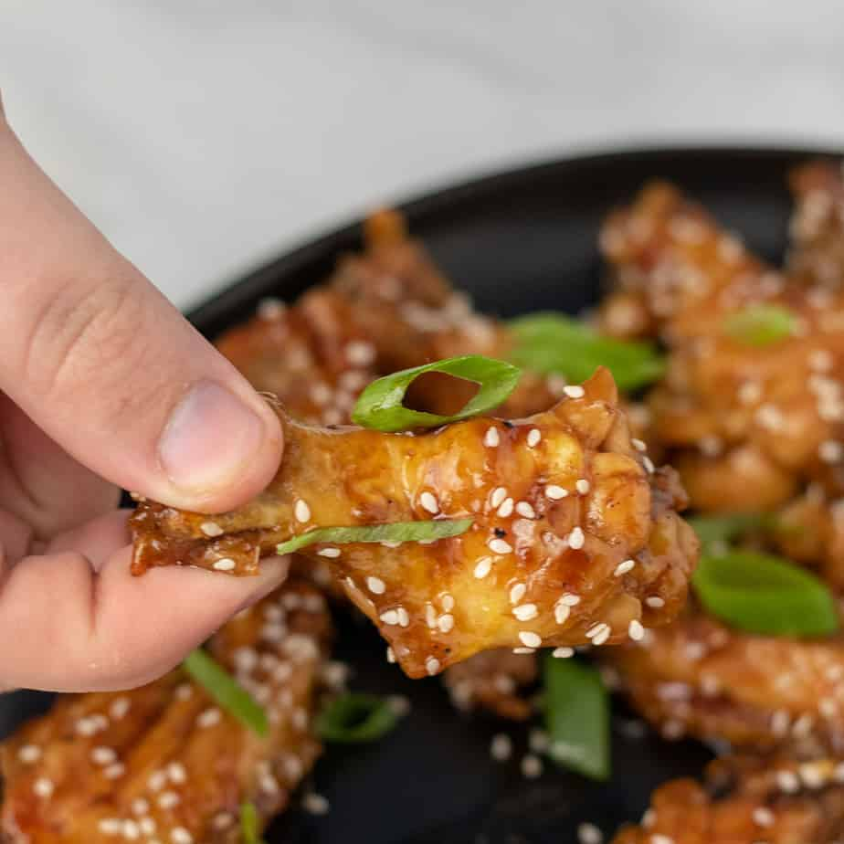 Chicken wing covered in teriyaki sauce, scallions and sesame seeds