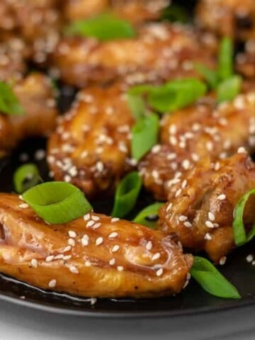 A plate of chicken wings with teriyaki sauce, sesame seeds and scallions.