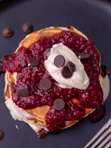 Top down view on pancakes on a black plate. Topped with raspberry, chocolate chips and mascarpone.
