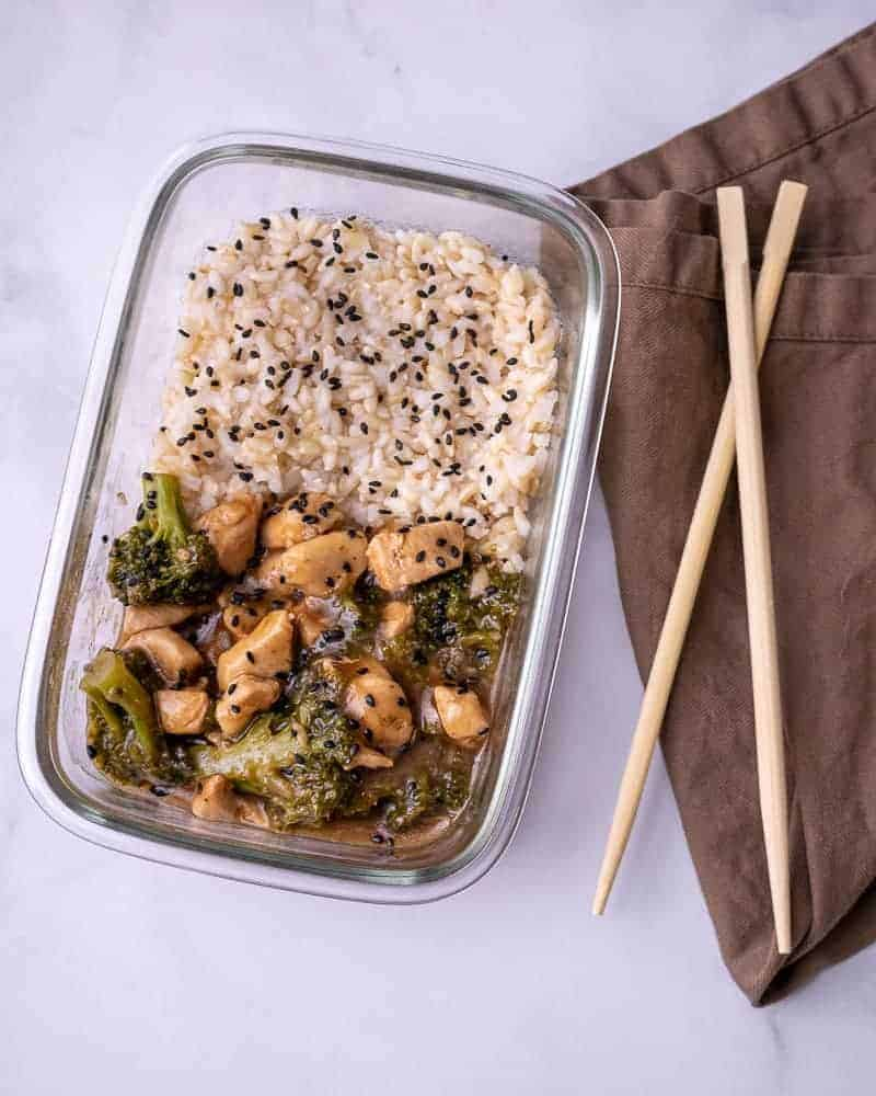 A close up of the meal prep container of chicken and broccoli with rice and oyster sauce. On a brown napkin with wooden chopsticks