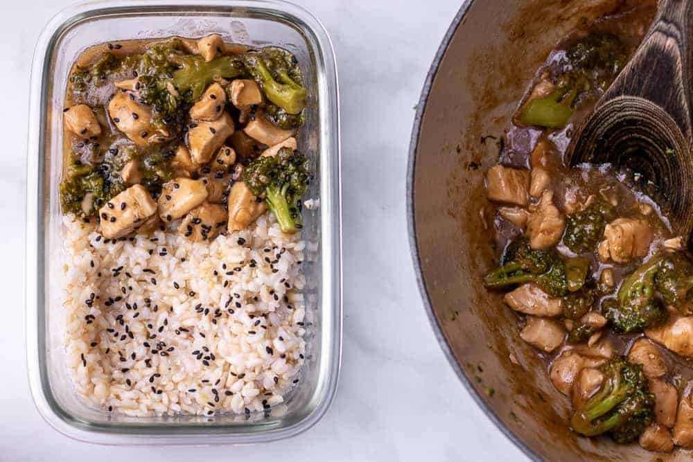 Chicken and broccoli over rice in a meal prep container next to a dutch oven full of chicken and broccoli in oyster sauce