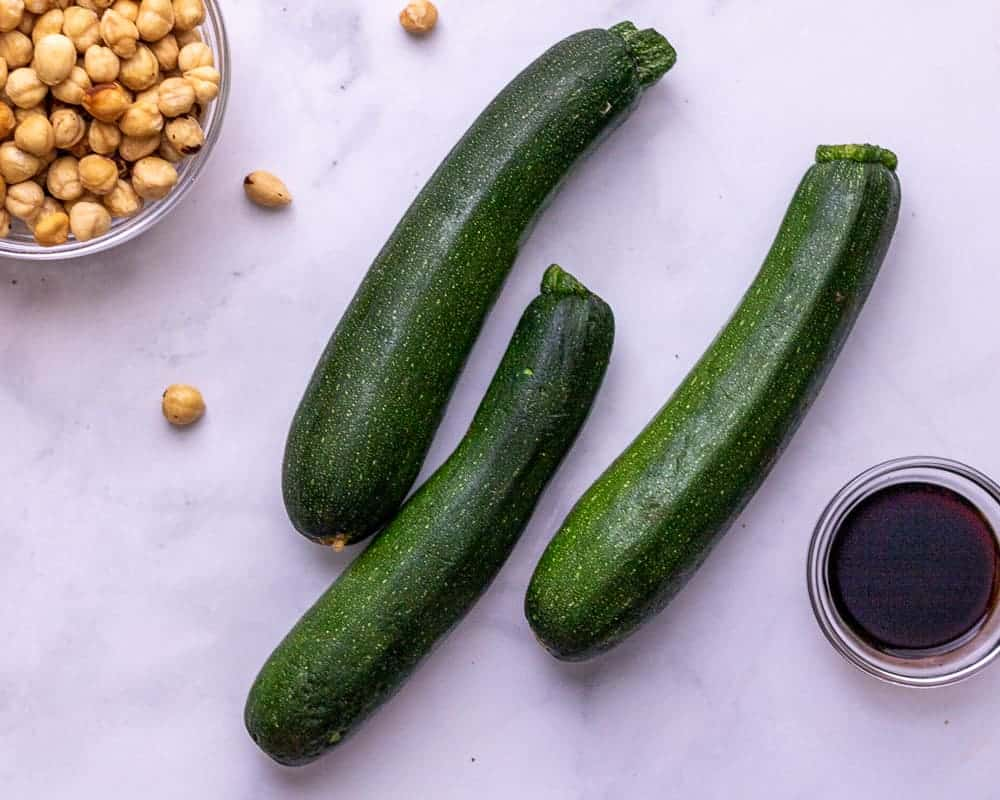 Raw zucchini in the center. A bowl of hazelnuts in the corner and a bowl of balsamic vinegar in the other corner.
