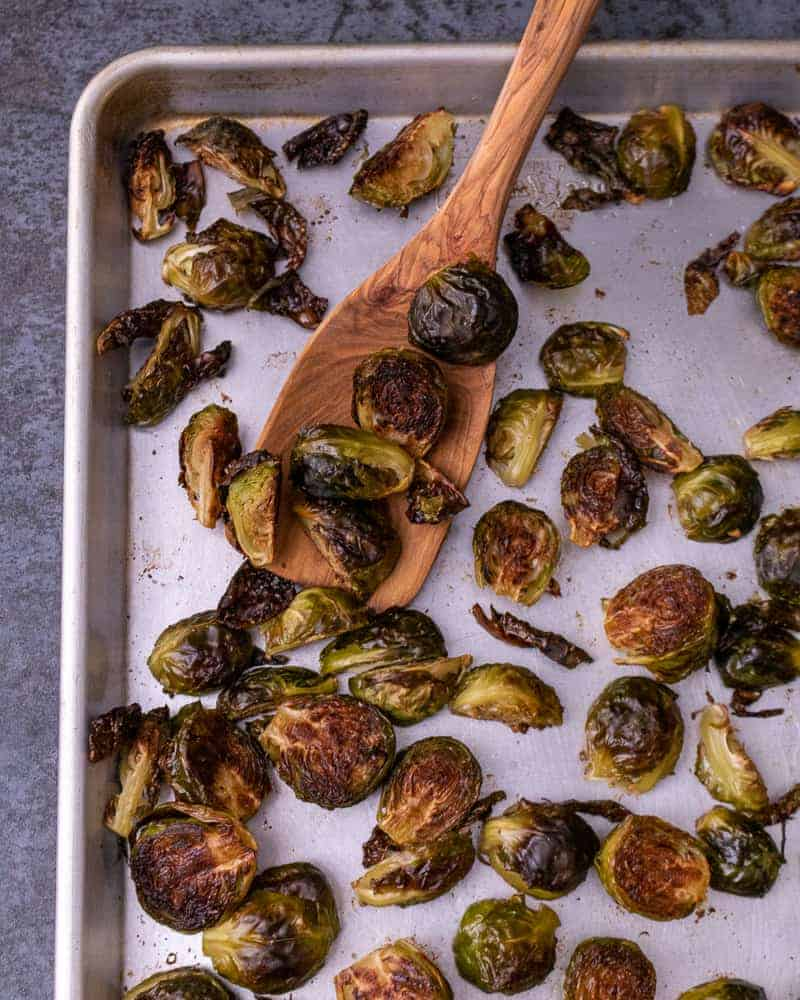 Close up of roasted brussel sprouts on a sheet tray with a wooden spoon