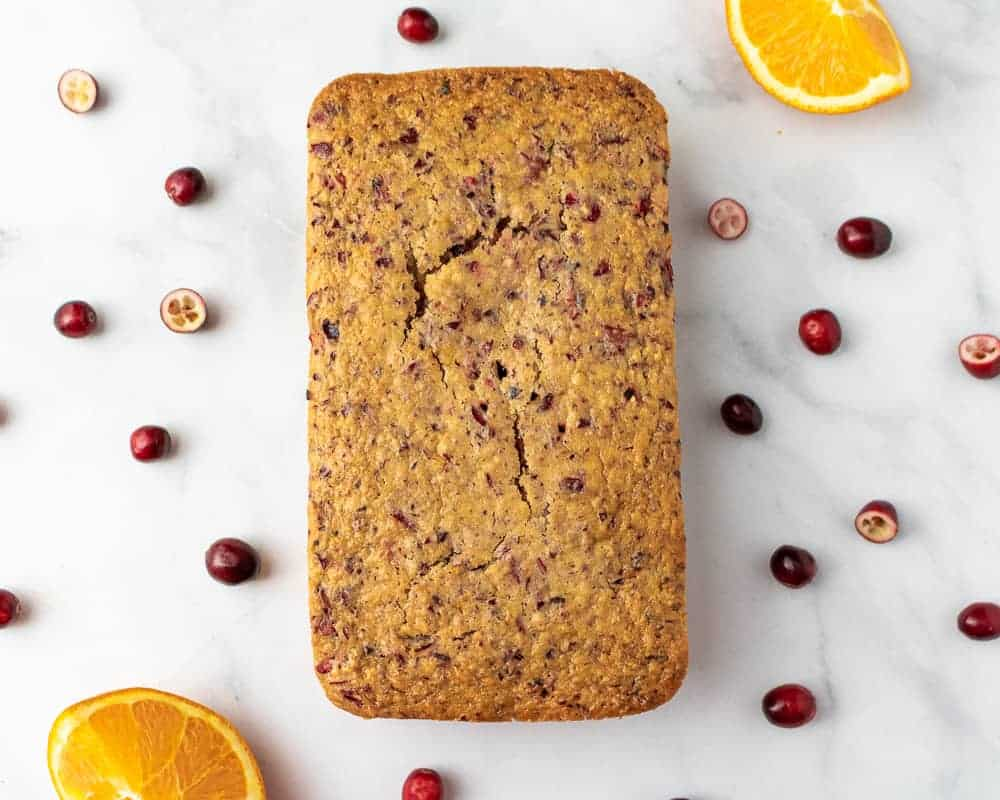 Overhead of a large loaf of cranberry bread with fresh oranges and cranberries scattered around