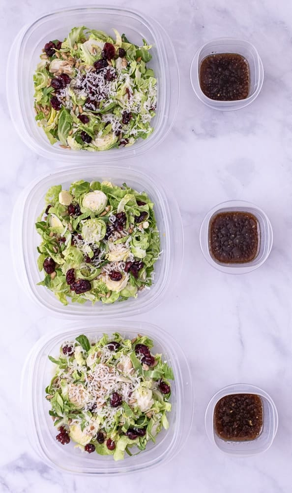 3 bowls of Shredded brussel sprouts with dressing on the side.