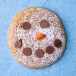A single close up of a snowman cookie on a blue background