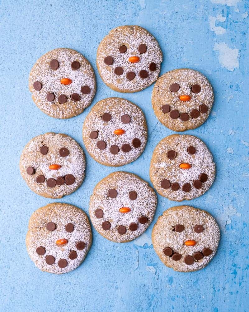 9 Snowman cookies in a cluster on a blue background