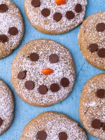 A close up of snowman cookies on a blue backround
