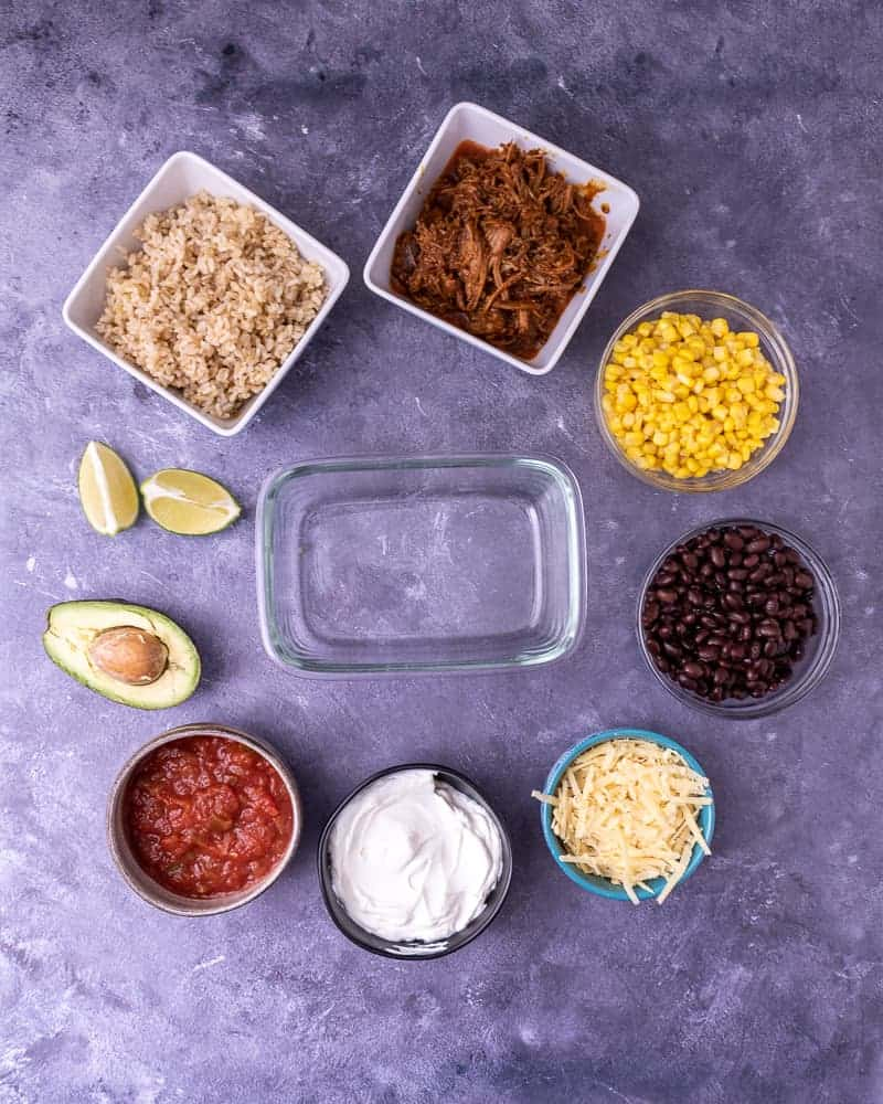 Ingredients laid out for pork burrito bowls around an empty meal prep container