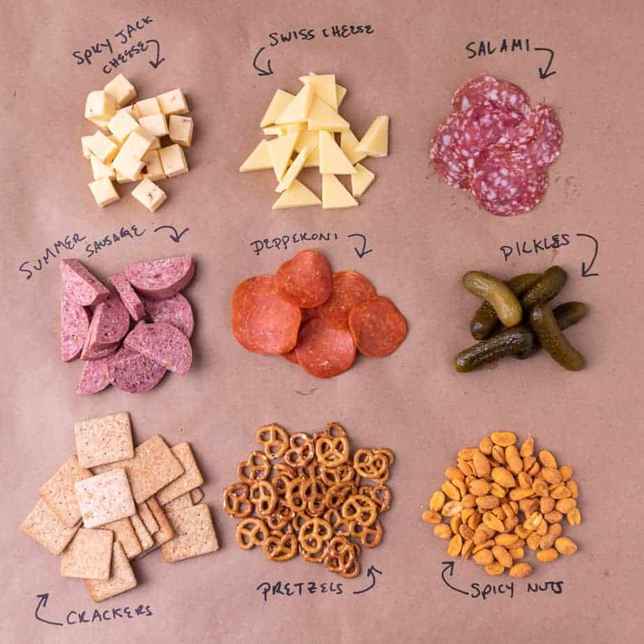 All 9 ingredients of the Super Bowl cheese board laid out and labeled on brown paper
