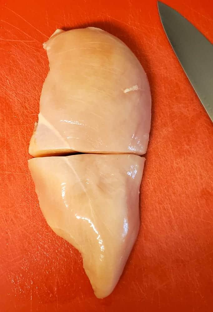 A raw chicken breast cut in half.