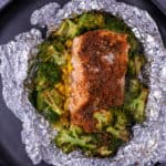 Close up of cooked cajun salmon in foil with veggies.