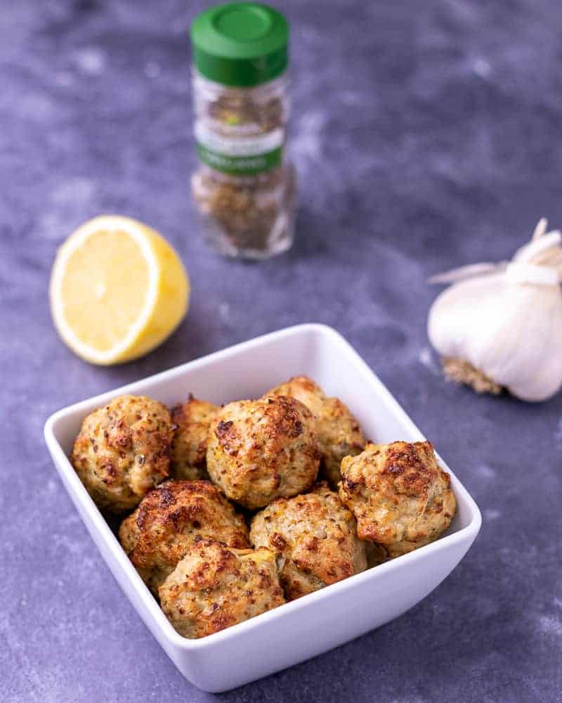 Greek chicken meatballs in the a bowl with ingredients in the background