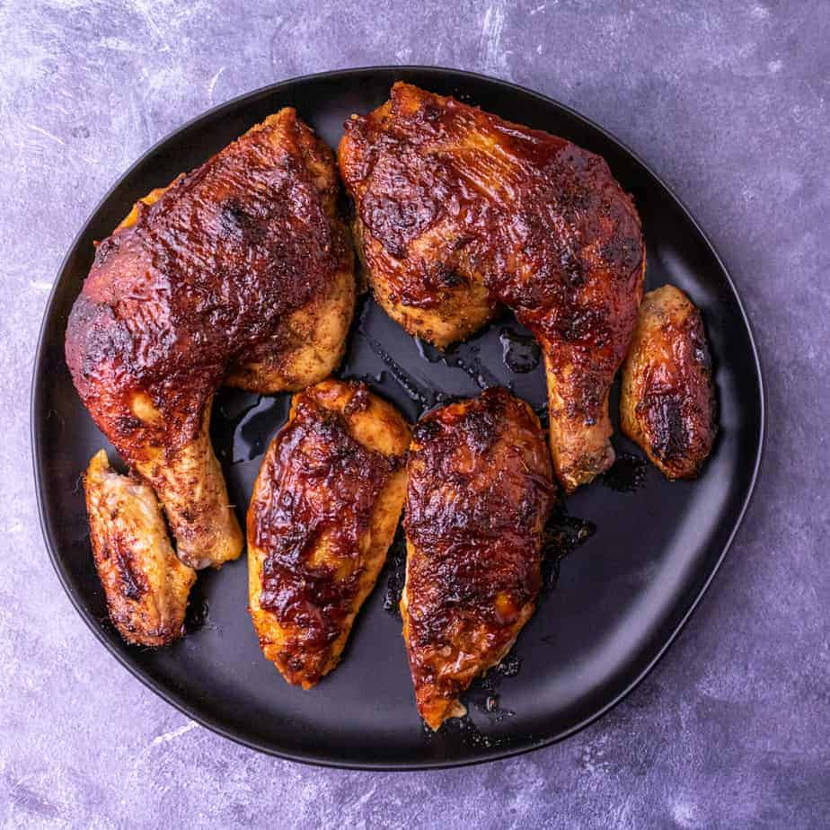 Roasted chicken cut up in pieces on a black plate.