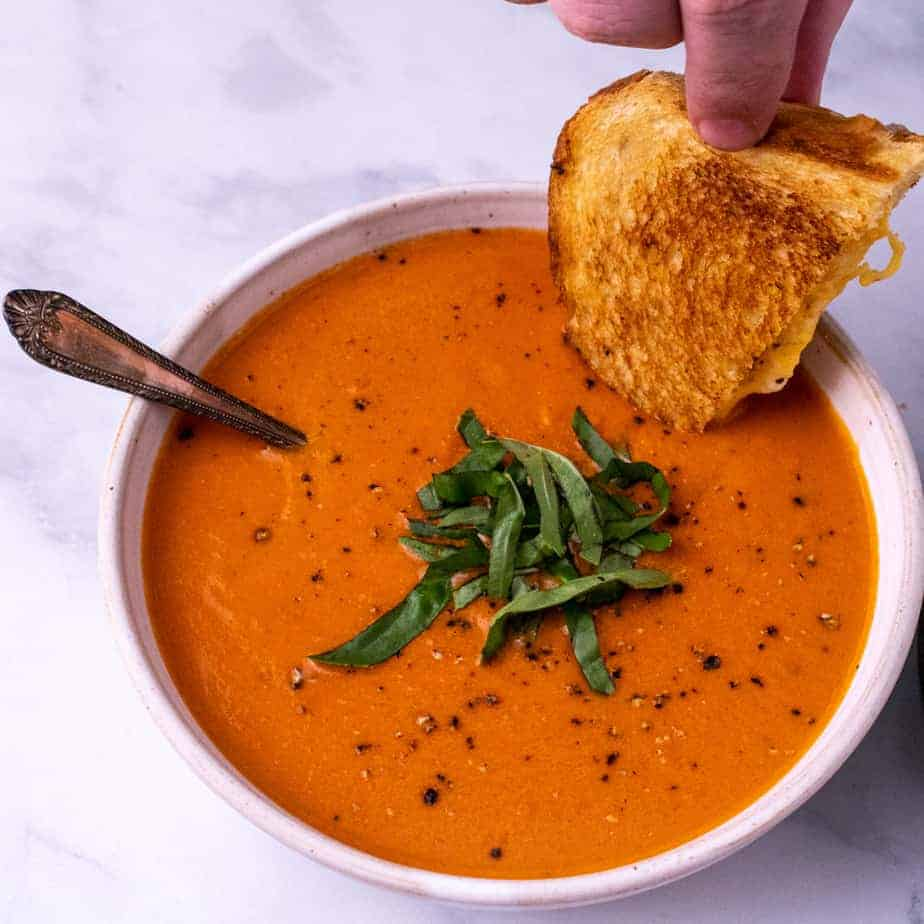 Grilled cheese being dunked into a white bowl of tomato bisque with a spoon and garnished with fresh basil. All on a white background.