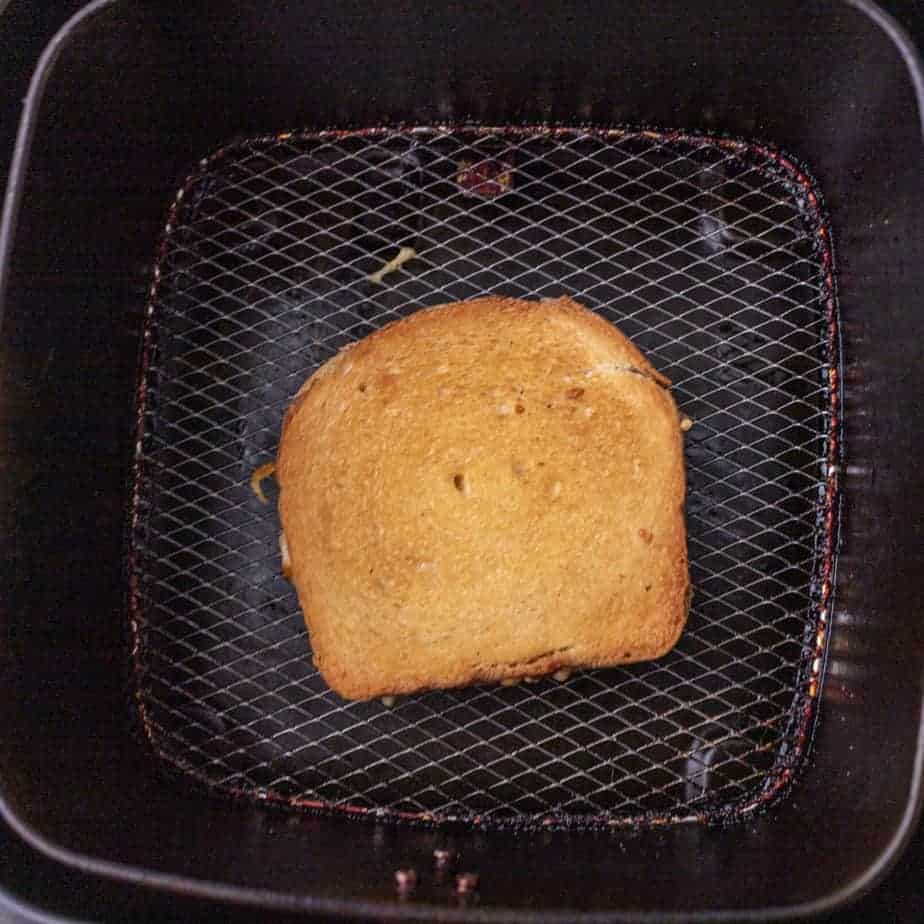 Grilled cheese in the center of an air fryer basket.