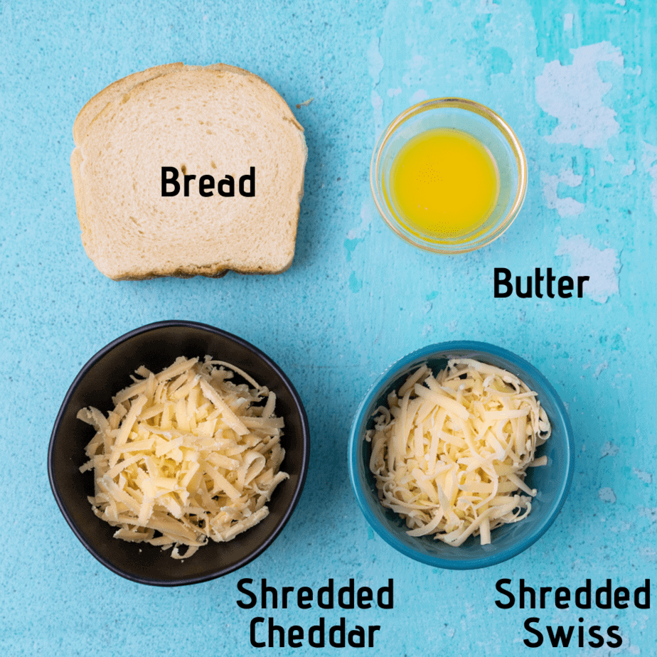 Ingredients laid out and labeled, bread, butter, shredded cheddar, shredded swiss. On a blue background.