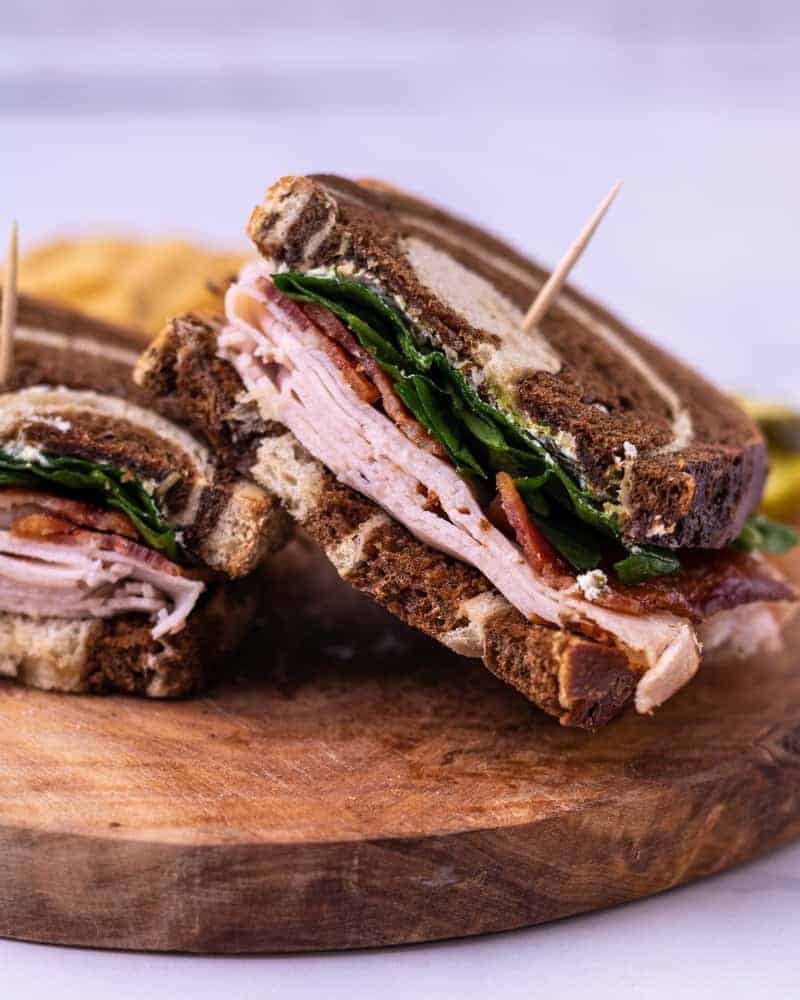 Turkey sandwich cut in half and skewered with a toothpick. Laying at an angle on a wooden plate.