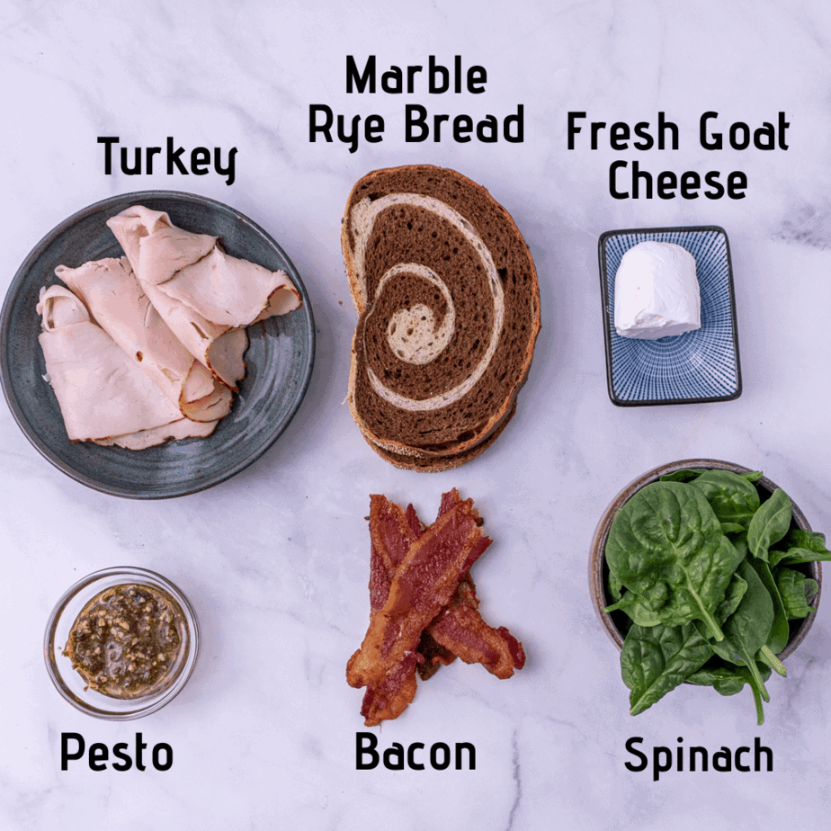 Ingredients laid out on a white background, labeled turkey, marble rye bread, fresh goat cheese, pesto, bacon and spinach.