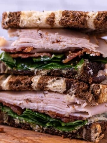 Two halves of the turkey sandwich stacked on top of each other on a wooden plate.