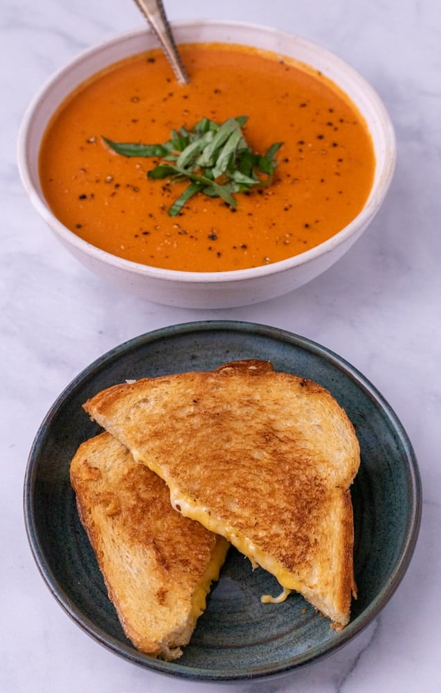 Grilled cheese sandwich cut diagonal on a green plate in front of awhite bowl of tomato soup