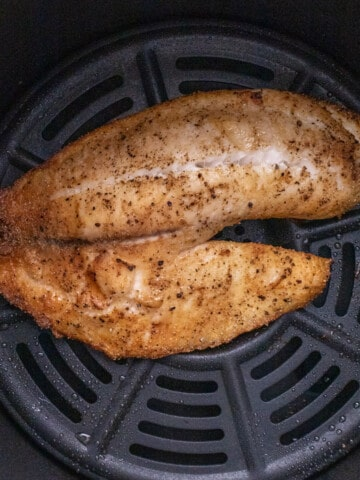 Tilapia on a plate with Roasted brussels sprouts and lemon on the plate