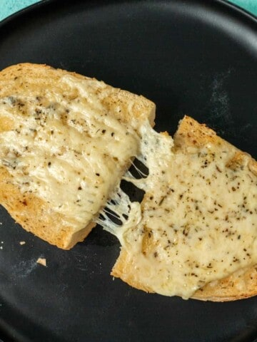 2 pieces of garlic bread being pulled apart to show a cheese pull on a black plate.