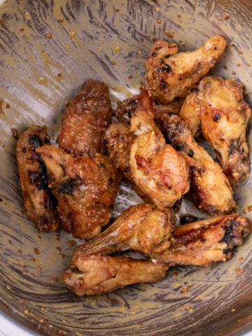 Sauced chicken wings on a black plate.