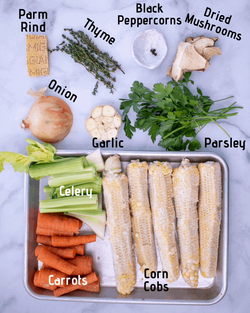 Raw ingredients laid out on a white background, parm rind, fresh thyme, black peppercorns, dried mushrooms, onion, garlic, fresh parsley, corn cobs, celery and carrots.
