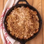Baked apple crisp in a cast iron skillet with a red and white napkin