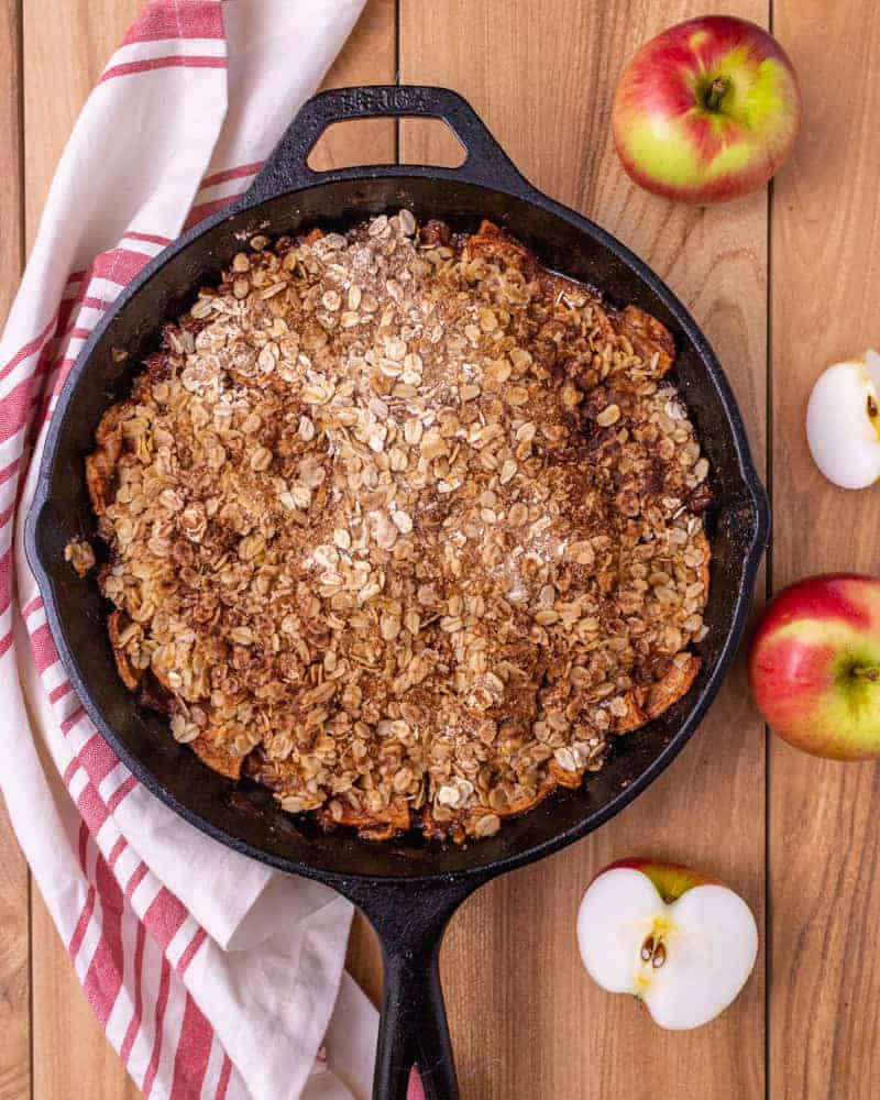 Baked apple crisp in a cast iron skillet with a red and white napkin and cut up raw apples.