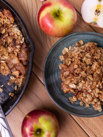 A slice of apple crisp on a plate surrounded by apples. A portion of the apple crisp in the skillet with a spoon