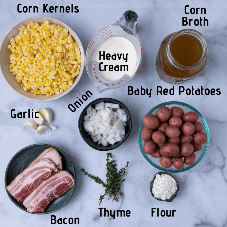 Raw ingredients laid out and labeled. Corn kernels, heavy cream, corn broth, garlic, onion, red potatoes, bacon, fresh thyme and flour.