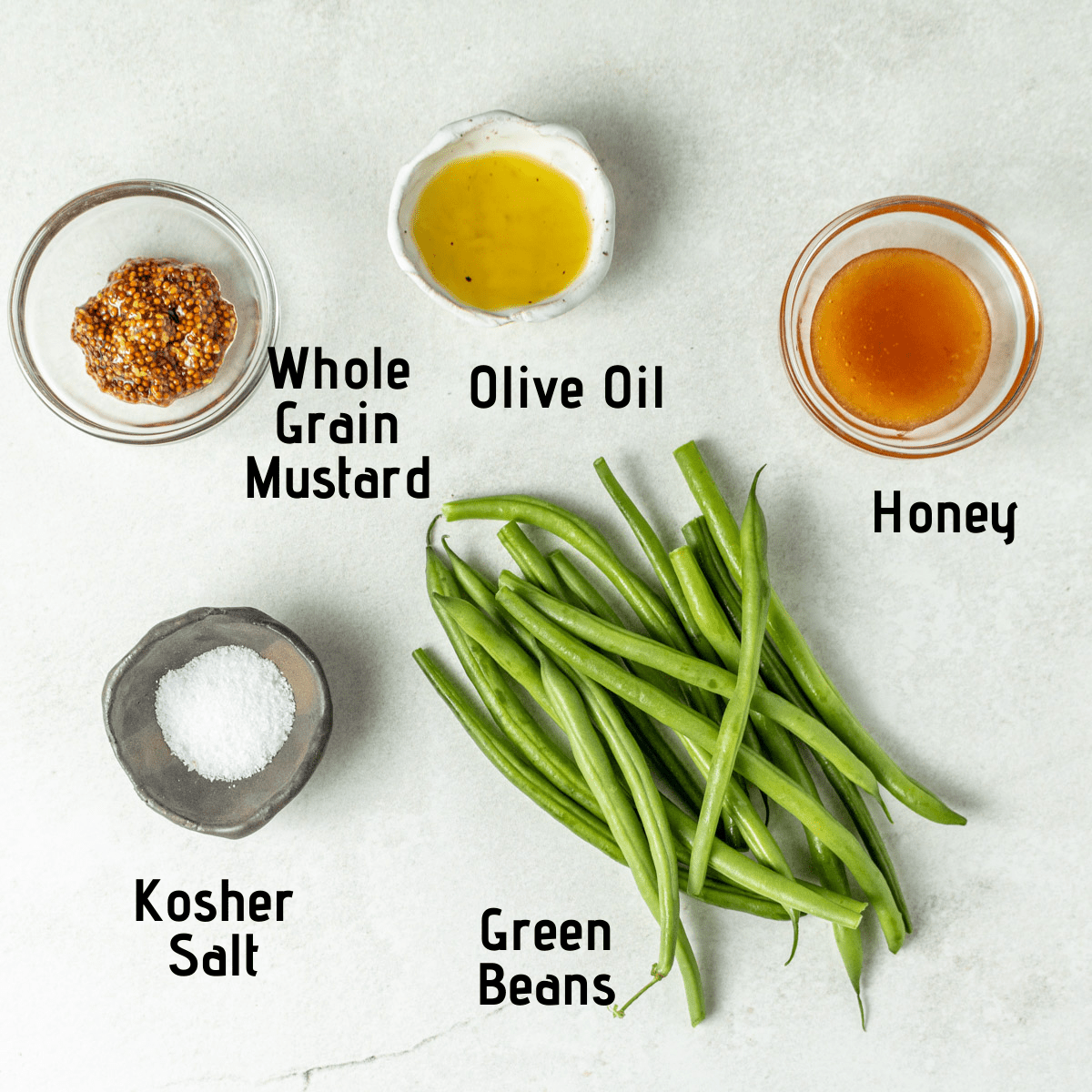 Raw ingredients laid out on a white background, labeled: whole grain mustard, olive oil, honey, kosher salt and green beans.