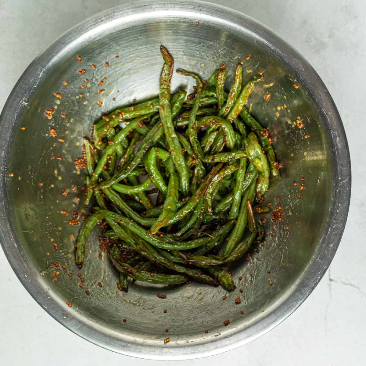 Cooked green beans in a large metal mixing bowl, tossed in mustard and honey. Set on a white background.