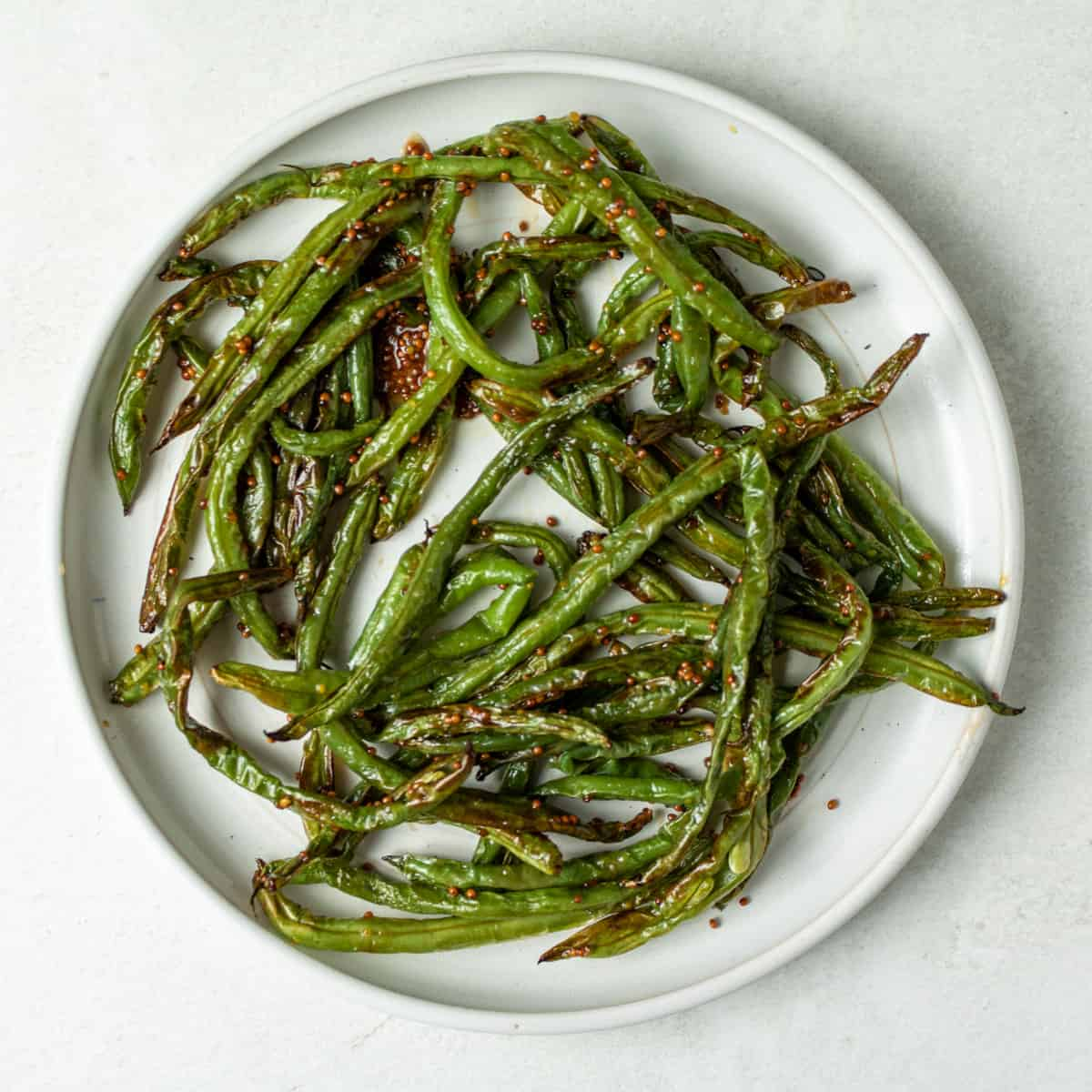 Cooked green beans on a white plate, tossed in whole grain mustard and honey.
