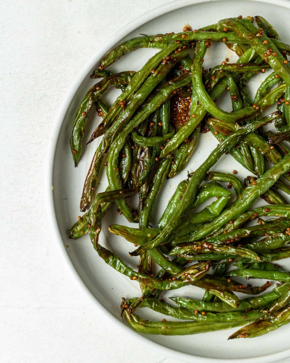 A close up but only partial view of cooked green beans tossed in combination mustard and honey. Green beans are on a white plate on a white backgroud.