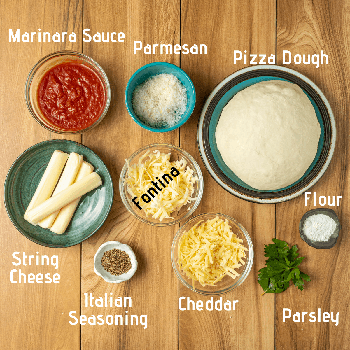 Raw ingredients laid out on a wood surface. Marinara sauce, parmesan, pizza dough, string cheese, fontina, flour, italian seasoning, cheddar and parsley