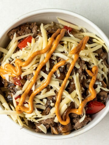 Assembled steak and rice bowl with chipotle mayo drizzled on top. In a white bowl on a white background.